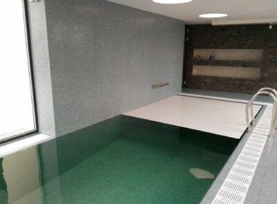 Jednoduchá bílá lamela na mozaikovém bazénu.