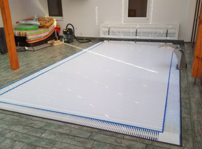 Atypické řešení krytu zavěšené na stěnu za bazénem